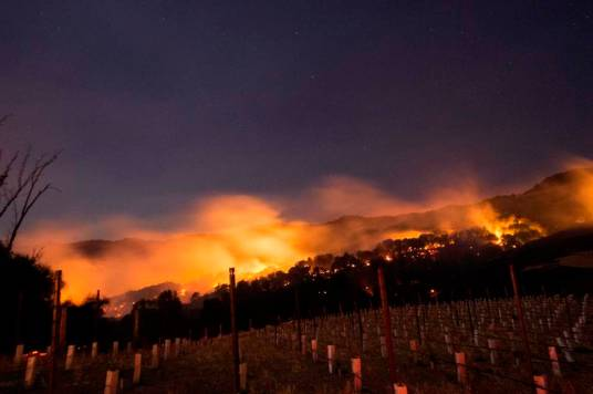 Fire glows on a hillside in Napa, California on October 9, 2017, as multiple wind-driven fires continue to whip through the region. / AFP PHOTO / JOSH EDELSON (Photo credit should read JOSH EDELSON/AFP/Getty Images)